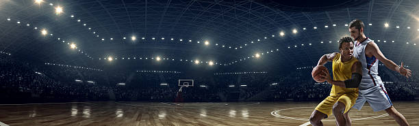 Panoramic basketball game moment Low angle panoramic view of a professional basketball game. A player failed to block the opposite team player with a ball. A game is in a indoor floodlit basketball arena. All players are wearing generic unbranded basketball uniform. jump shot stock pictures, royalty-free photos & images