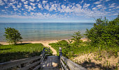 Stairs lead to a beautiful sandy beach with crystal clear blue water and a sunny summer blue sky at the horizon. Northern shore of Lake Michigan in the Upper Peninsula.