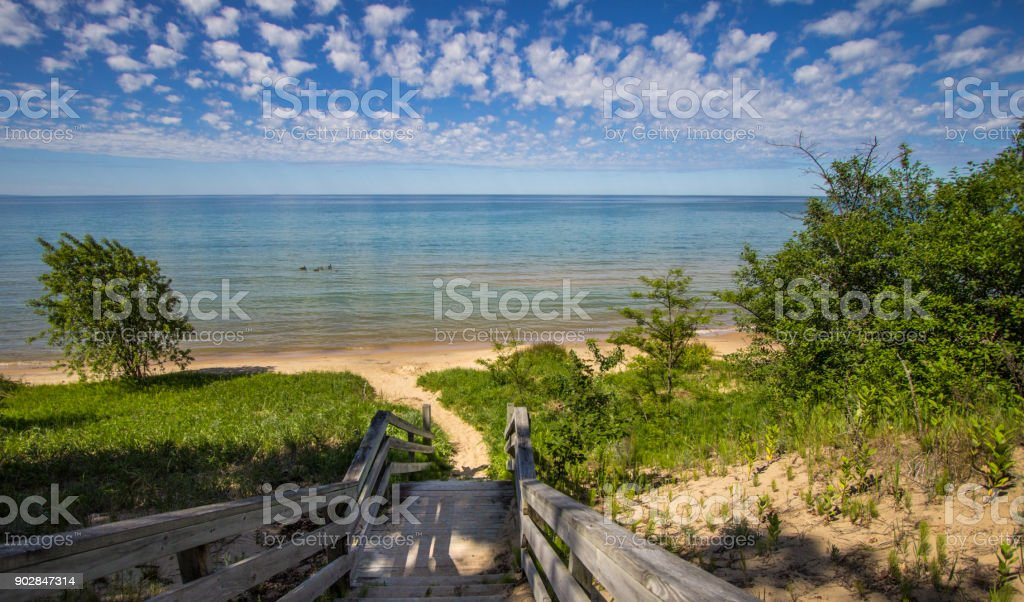 Panoramic Beach Scene With Sunny Summer Blue Sky And Stairs Leading To The Beach On Lake Michigan stock photo