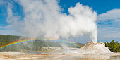 Panoramic photograph of the famous Castle Geyser with eruption and rainbow in the Upper Geyser Basin of Yellowstone national park, Wyoming, United States of America, USA.