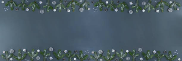 Panoramic Christmas frame made of fir branches decorated ,Silver pine cones, with Christmas ball and gift box on grey slate. Xmas backdrop for your greeting card space for text stock photo