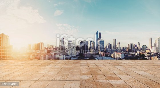 istock Panoramic city view in sunrise with empty wooden floor 691394812
