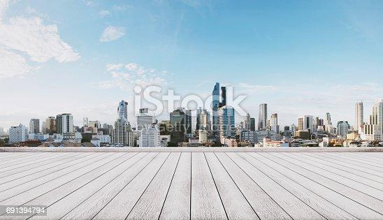 693903950istockphoto Panoramic city view with empty white wooden floor 691394794