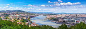 Panoramic cityscape view of hungarian capital city of Budapest from the Gellert Hill. The bridges connecting Buda and Pest across the river Danube. Summertime sunshine day, blue sky and green of trees