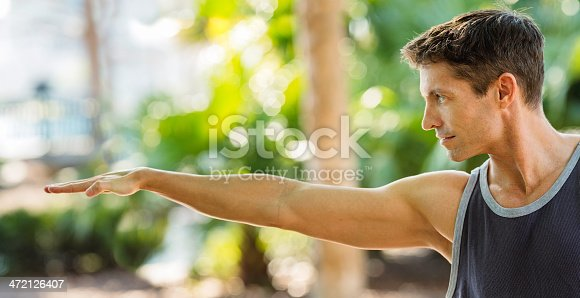 Partial image of young, fit man from chest level to head with one arm outstretched and hand extended.  He is looking straight ahead and he's wearing a dark-colored sleeveless T-shirt. The image is outside with a background of sunlight filtering through trees and vegetation.