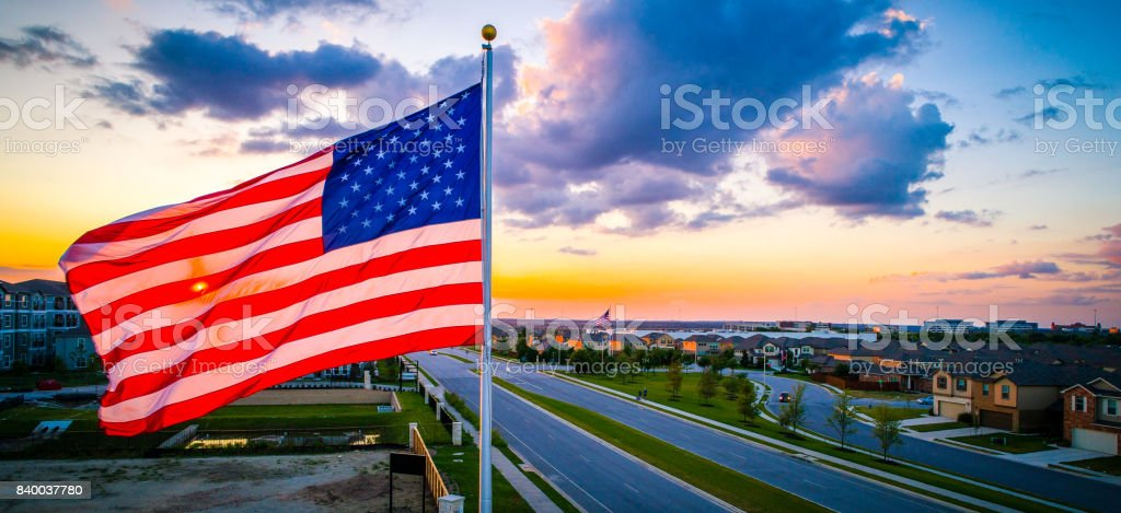 Panoramic Colorful American Pride United States Flag Flying during amazing colorful Sunset stock photo