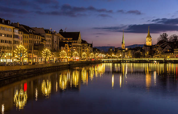 Panoramic evening view of Zurich on the Limmat river Zurich on banks of Limmat river at winter evening limmat river stock pictures, royalty-free photos & images