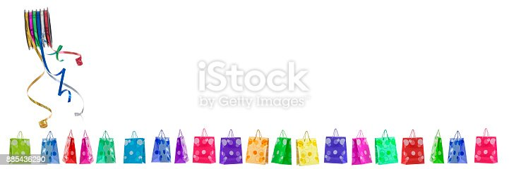 istock Panoramic festive image with rolls of curly ribbons on ltop efts corner and multi coloured gift bags on the gound on white 885436290
