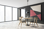 Corner of spacious panoramic dining room with gray walls, wooden floor, round table with grey chairs and abstract picture and window with blurry cityscape. 3d rendering
