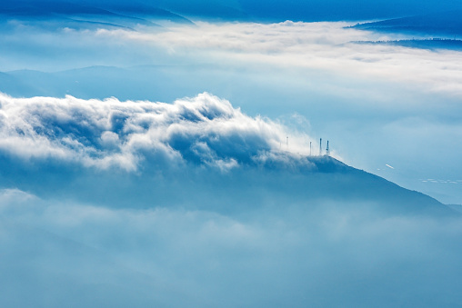 Landscape shot of mountains and dramatic clouds mixed with fog in winter