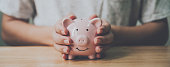 istock Panoramic image, Man hand holding piggy bank on wood table. Save money and financial investment 1191799062
