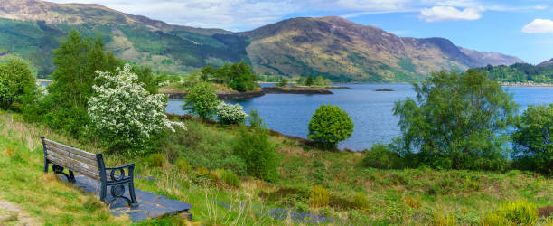 panoramabild des schönen loch leven mit blick auf eilean munde oder die grabinsel im sommer, glencoe, schottland - see loch leven stock-fotos und bilder