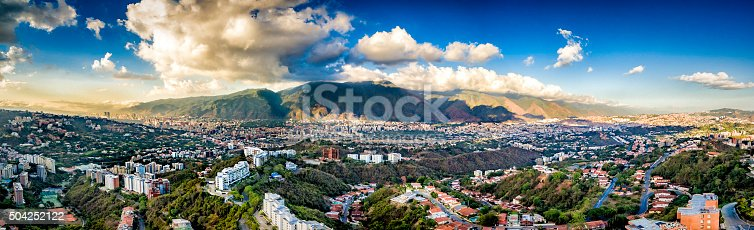 Panoramic image of eastern Caracas city aerial view at late afternoon. Venezuela.  Showing El Avila mountain also known as El Avila National Park (Guaraira Repano).  Santiago de Leon de Caracas, is the capital city of Venezuela and center of the Greater Caracas Area. It is located in the northern part of the country, following the contours of the narrow Caracas Valley and the