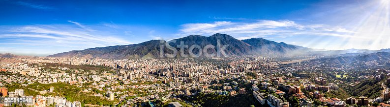 Panoramic image of eastern Caracas city aerial view at early morning. Venezuela.  Showing El Avila mountain also known as El Avila National Park (Guaraira Repano).  Santiago de Leon de Caracas, is the capital city of Venezuela and center of the Greater Caracas Area. It is located in the northern part of the country, following the contours of the narrow Caracas Valley and the
