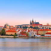 Panoramic image of Romantic Prague at dawn. Vltava riverside on sunrise, with Charles Bridge on the left and historic skyline with St. Vitus cathedral and castle.