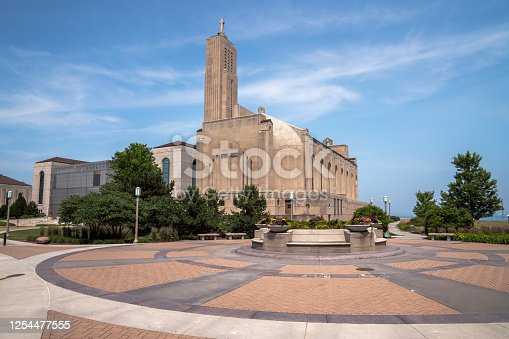 Panoramic image of the art deco Madonna della Strada Chapel on Loyola University campus on Lake Michigan with the sun in the blue sky above and beautiful masonry plaza below.