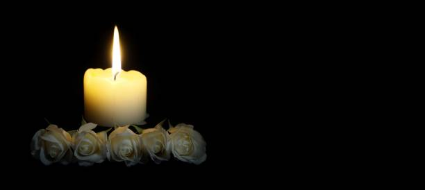 panoramic image of White roses and burning candles on table in darkness, Copy space for text. candles burning in the black background. Funeral symbol. The concept of mourn, grief or mourning. stock photo