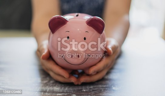 Panoramic image. Woman hand holding piggy bank on wooden table. Save money and financial investment concept. Investment concept. Hands holding a Piggy bank. pink piggy bank on a white background.coin making interest on the market. Business startup. loan concept and wealthy business growth.