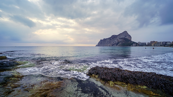 Panoramic landscape in the sea with a large mountain on the horizon and waves breaking against the rocks.