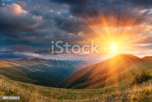 Panoramic landscape of fantastic sunset in the mountains. View of the autumn hills lit by the rays of the evening sun. Dramatic clouds over sky.