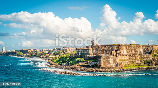 Colorful image with fortification Castillo San Felipe del Morro along the coastline in San Juan, Puerto Rico.  Blue sky and white clouds.