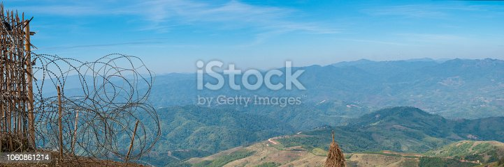 587773316 istock photo panoramic landscape scenery at Thailand and Myanmar borderline in Chiengrai with barbed wire fence and background of mountains and blue sky 1060861214