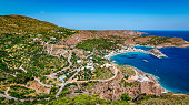 Bright and colorful panoramic landscape of Kapsali, Kythira, Greek Islands. Aerial view with bay of water, harbor or port, beach, mountains and green nature.