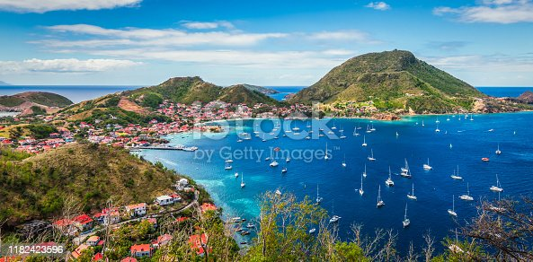 Colorful image of Guadeloupe Terre de Haut bay and town with buildings along the coastline. Small ships anchored in port. Cruise destination. Green mountains in the background. Blue sky and some white clouds.
