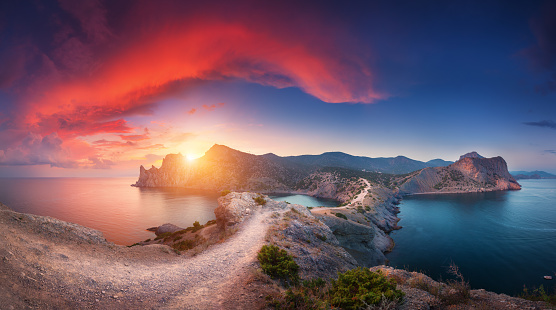 Amazing summer landscape with mountains, sea, blue sky, sun and beautiful colorful red clouds at sunset in Crimea. Sunset in mountains. Panoramic. Nature background. Vibrant landscape in twilight.