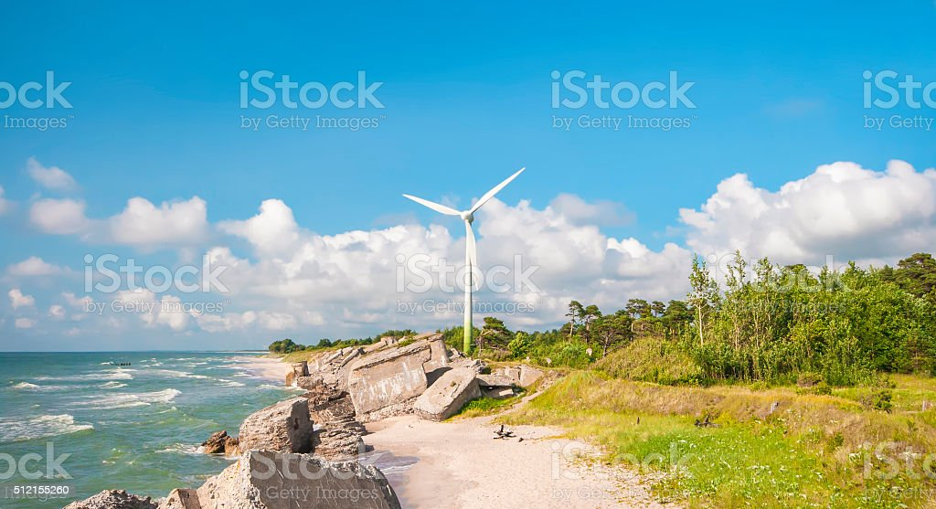 Panoramic landscape with windmill, sea, forest, stones and clouds stock photo