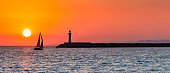 Beautiful panoramic view of an ocean sunset, with silhouettes of sail boat and lighthouse against an orange sky.