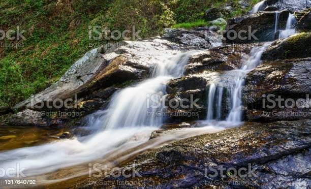 Photo of Panoramic of fresh water waterfall coming down from the mountain in long exposure photo. Navacerrada Madrid.