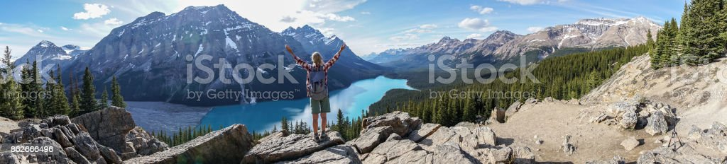 Young woman hiker arms outstretched above mountain lake in...