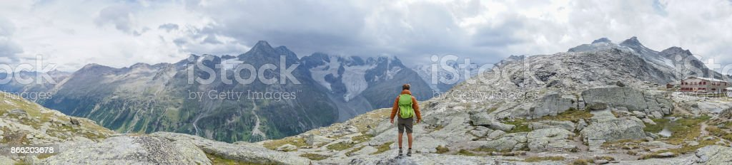 Panoramic of male hiking in Switzerland looking at mountain view stock photo