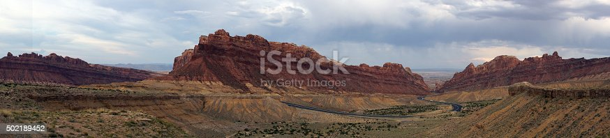 Panoramic of Road winds through Spotted Wolf Canyon with dramatic clouds in sky in Utah, USA.