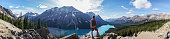 Young man hiker on rock above mountain lake in Springtime. People success in nature concept