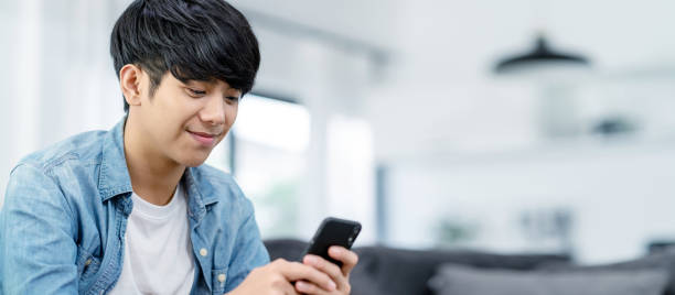 Panoramic or Banner of Happy asian teenager using smart phone and smiling on sofa living room at home. Asian man holding and using cellphone for searching data and social medie on internet. stock photo