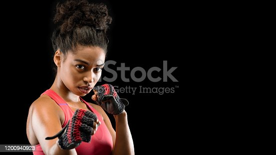 Portrait of beautiful african athletic fighter woman wearing gloves during training, copy space. Female martial arts