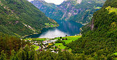 A panoramic photo of the Geirangerfjord in Norway is taken on a summer day. The scene is mainly green. In the valley on the fjord shore, there are tourist buildings and a body of water surrounded by a mojestic mountain range.