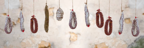 Panoramic Selection of French dry charcuterie hanging over old brown white cracked wall background. stock photo