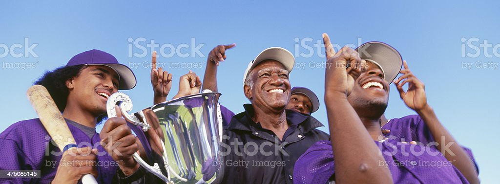 Panoramic shot of cheerful baseball players with trophy royalty-free stock photo