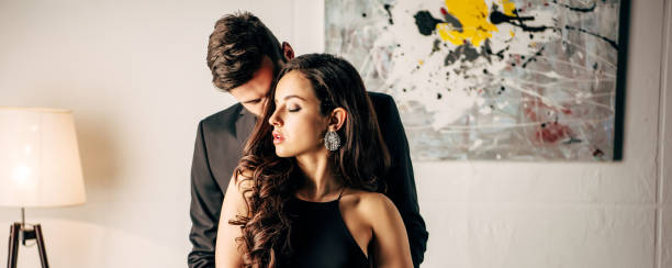 panoramic shot of handsome man in suit standing with beautiful woman in black dress - seduzione foto e immagini stock