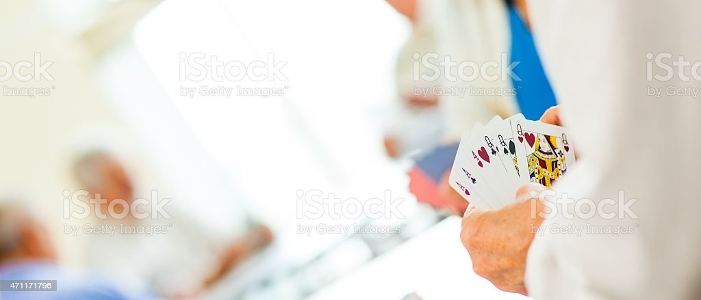 Panoramic shot of seniors playing cards stock photo