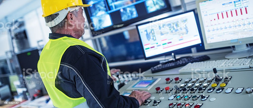 Panoramic shot of technician in control room stock photo
