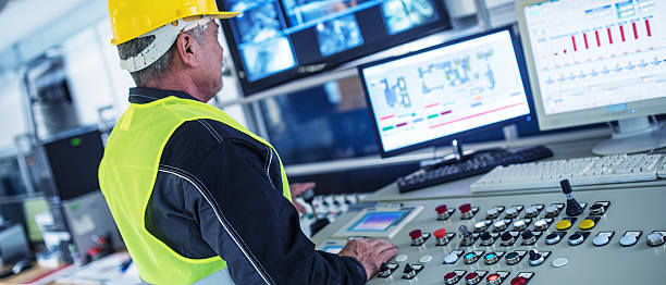 panoramic shot of technician in control room - control panel stock photos and pictures