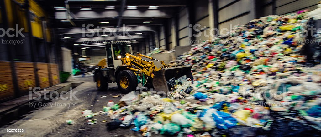 Panoramic shot of the earth mover in the garbage dump stock photo