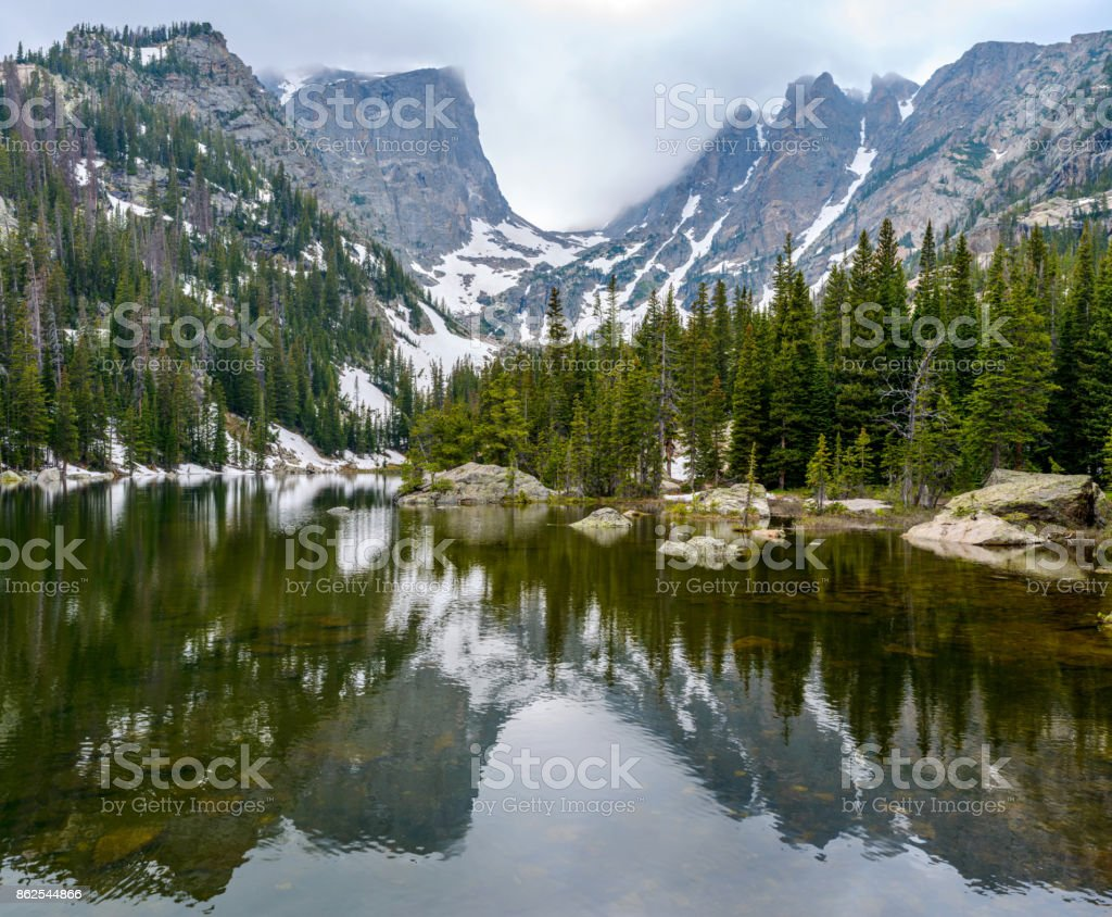 A panoramic spring view of Dream Lake, with Hallett Peak (12,713 ft) and Flattop Mountain (12,324 ft) rising high in the background, Rocky Mountain National Park, Colorado, USA. stock photo