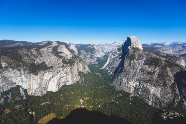 panoramic summer view of yosemite valley with half dome mountain, tenaya canyon, liberty cap, vernal fall and nevada fall, seen from glacier point overlook, yosemite national park, california - granite rock stock photos and pictures