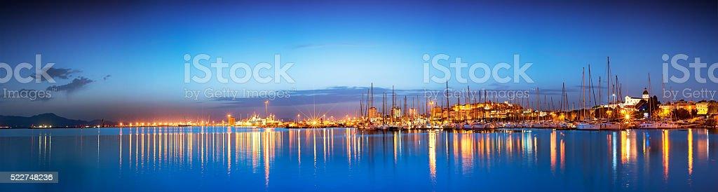 Panorâmica da cidade ao pôr-do-sol no mar com reflexo - foto de acervo