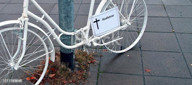 istock panoramic view and close up of a funeral ghost bike memorial with a german sign - Radfahrer - cross for a killed cyclist. German city street on a rainy Day. memorial to a cyclist who died in traffic accident 1211193646